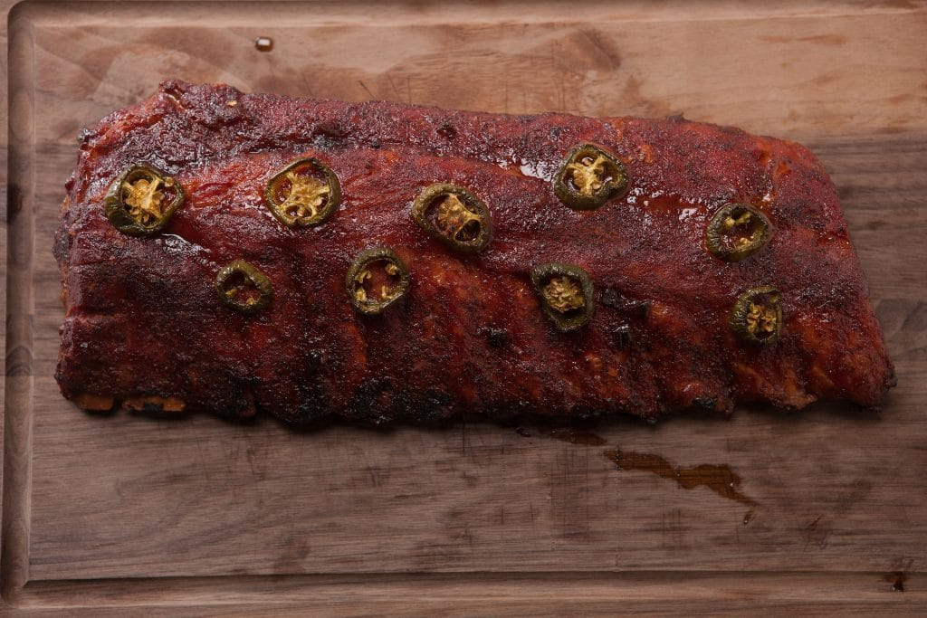 Overhead view of rack of smoked ribs topped with jalapeno slices on a wood cutting board.