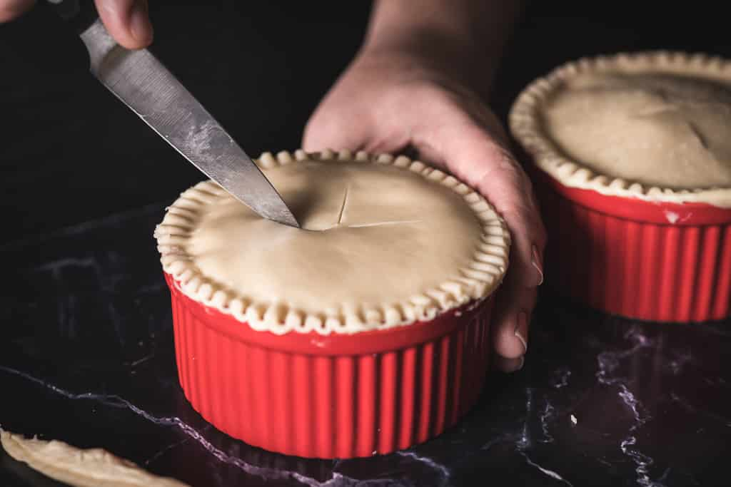 Knife scoring the top crust of a Guinness and steak pot pie