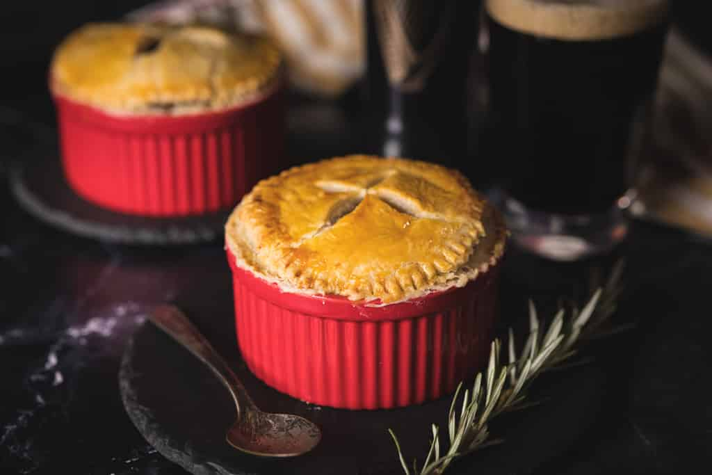 Two Guinness and beef pot pies on a dark marble surface.