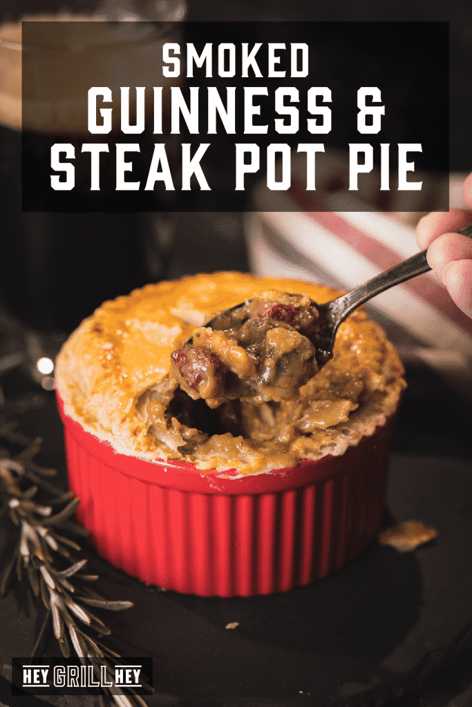 Metal spoon taking a scoop out of a red ramekin filled with beef pot pie. Text overlay reads: Smoked Guinness & Steak Pot Pie.