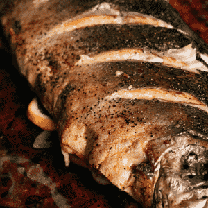 Grilled whole salmon on peach butcher paper with text overlay - Grilled Whole Salmon.