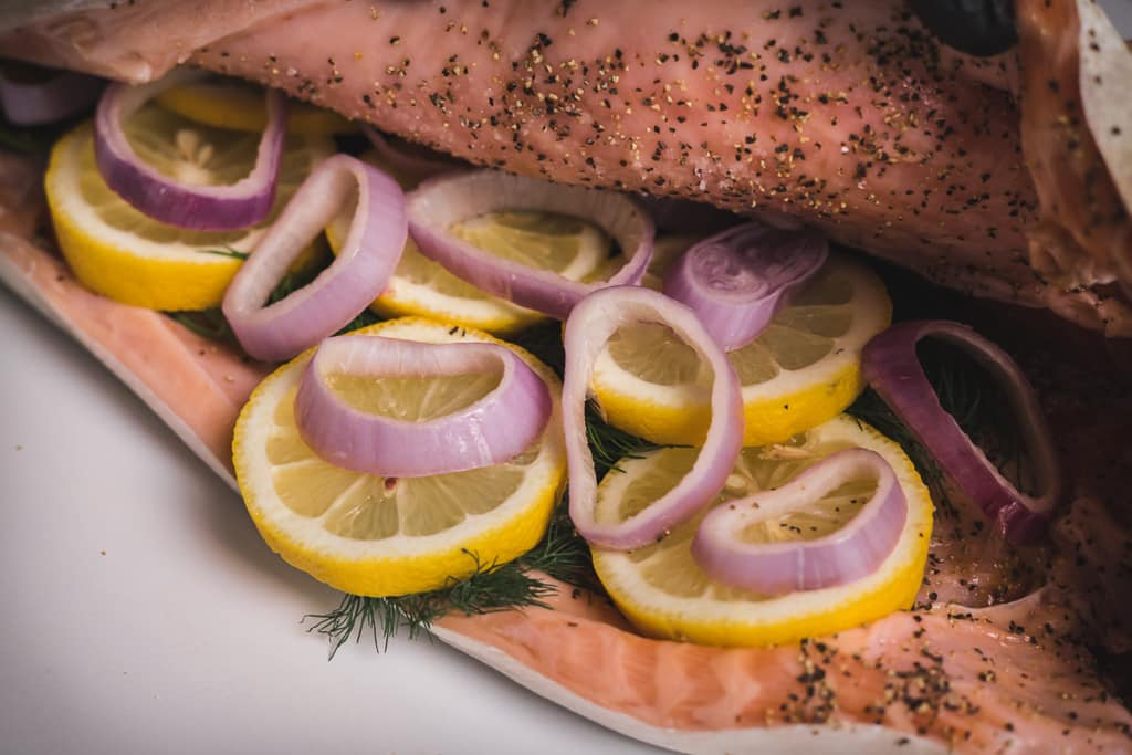 Sliced lemon and shallots in a whole salmon.