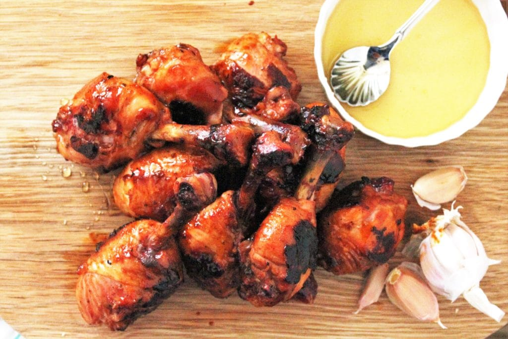 Aerial view of chicken lollipops arranged on a wood cutting board next to a bulb of garlic and a small white bowl of honey.