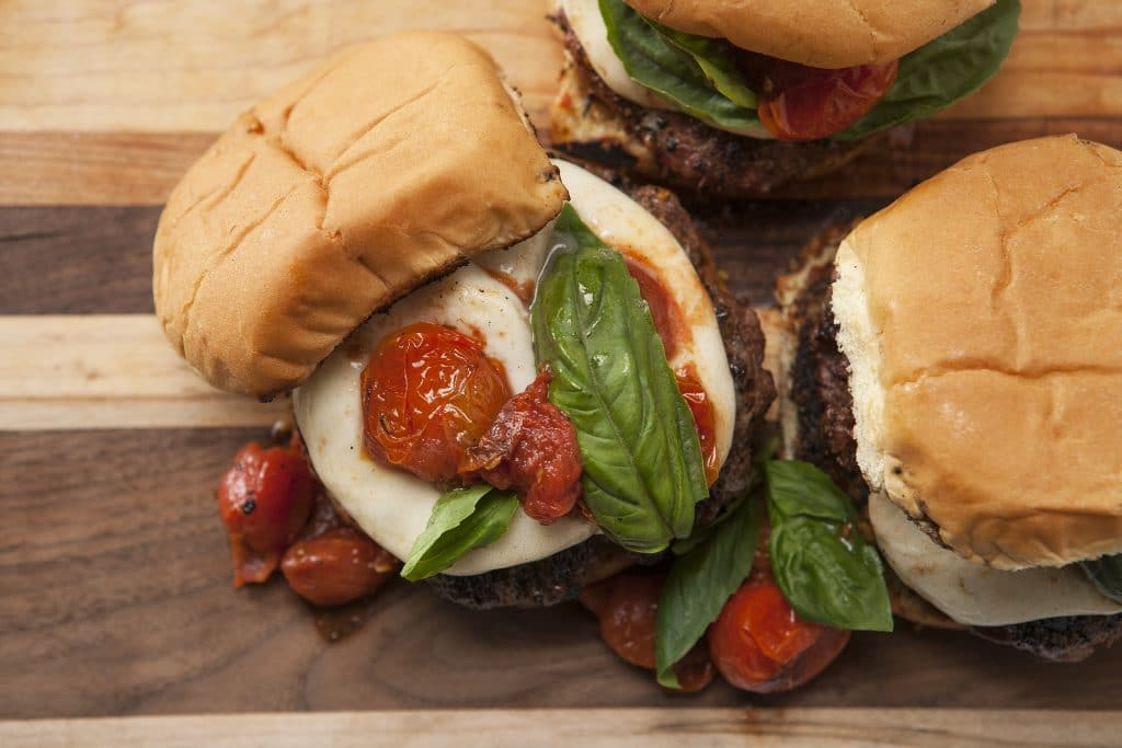 Overhead view of garlic butter burger topped with mozzarella, tomatoes, and basil.