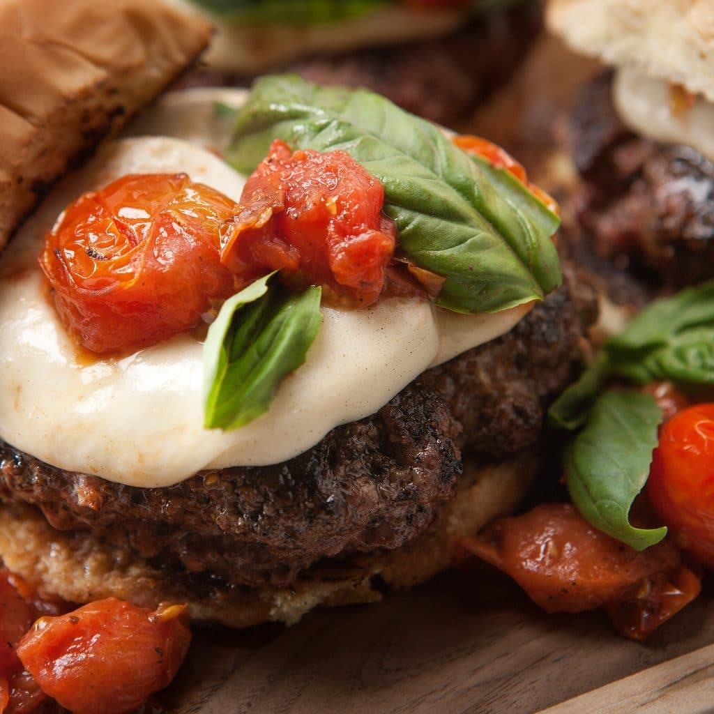 hamburger topped with mozzarella cheese, cherry tomatoes, and spinach.