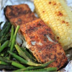 Grilled asparagus, seasoned whole salmon, and an ear of corn on a sheet of aluminum foil.