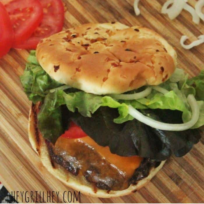 burger on a bun with lettuce, cheese, onion