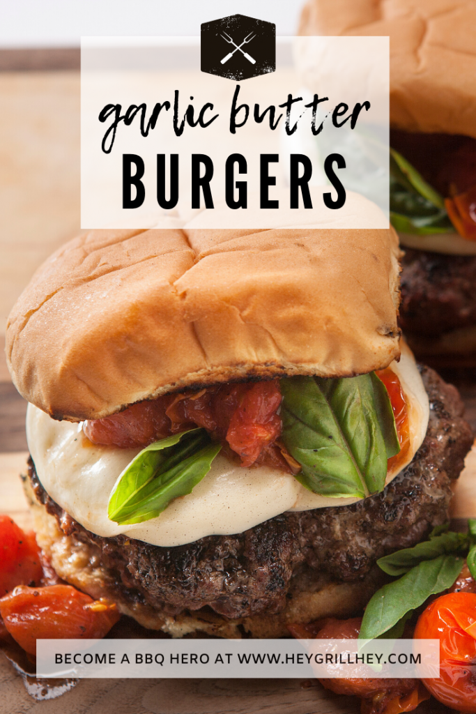 Garlic butter burgers topped with mozzarella, basil, and grilled tomatoes on a wood cutting board.