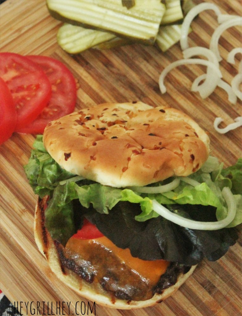 Cheeseburger with bun and toppings on a wood cutting board with more toppings arranged around it.