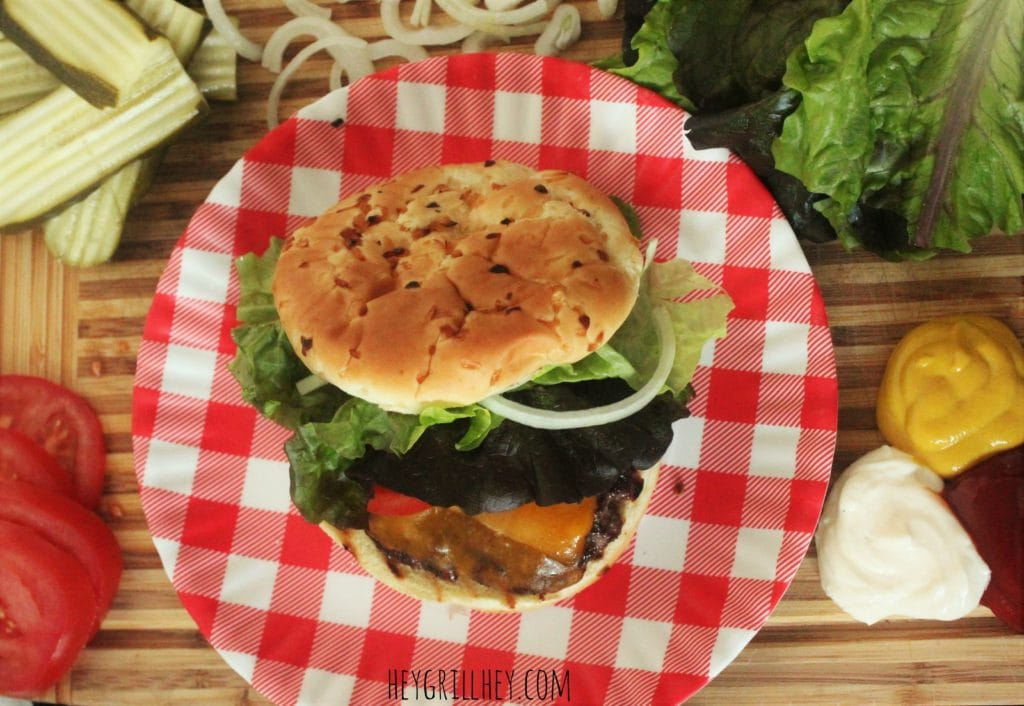 Cheeseburger with bun and toppings on a red and white plate with more topping arranged around on a wood cutting board.