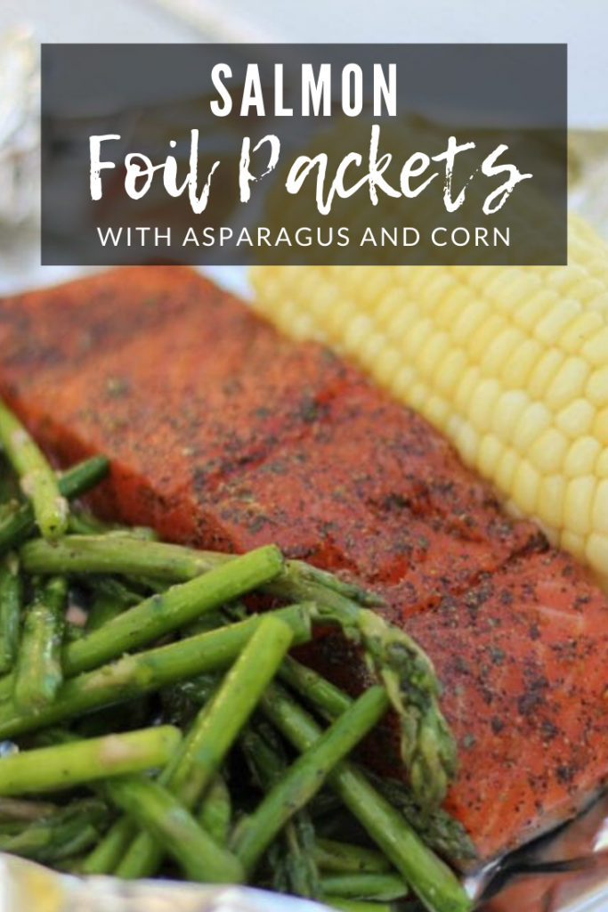 """Grilled asparagus, seasoned whole salmon, and an ear of corn on a sheet of aluminum foil with the text overlay: """"Salmon foil packets with asparagus and corn."""""""