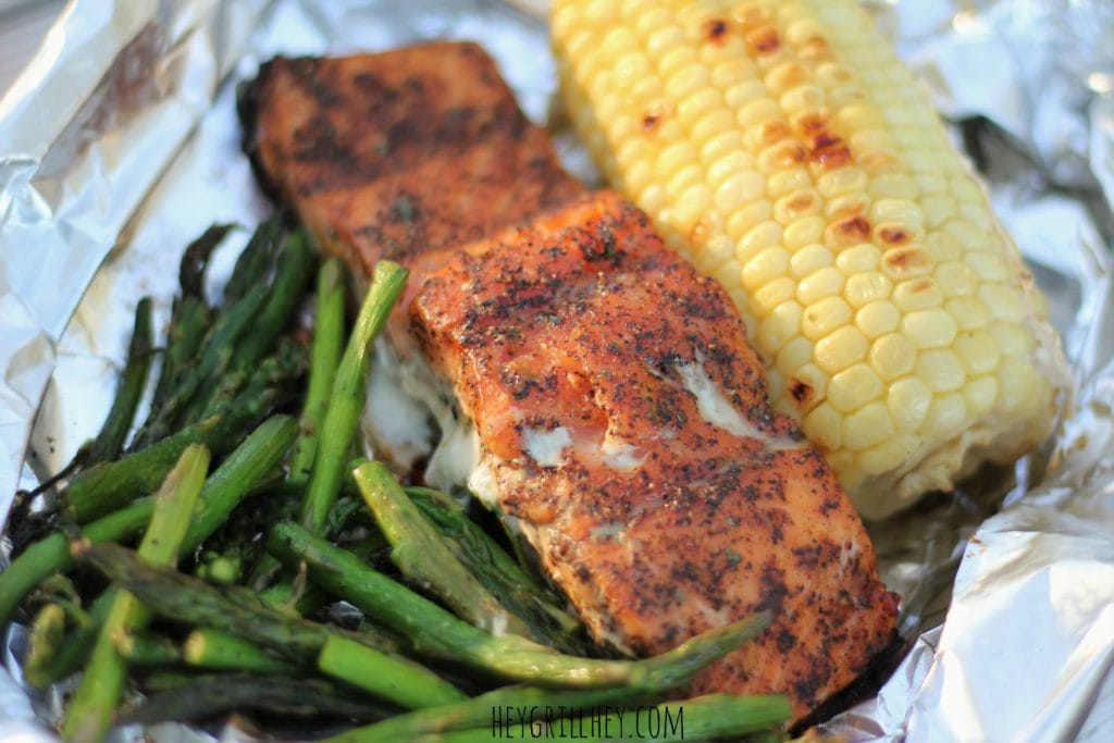 Close up of grilled asparagus, seasoned and grilled salmon, and a half ear of grilled corn in a aluminum foil packet.