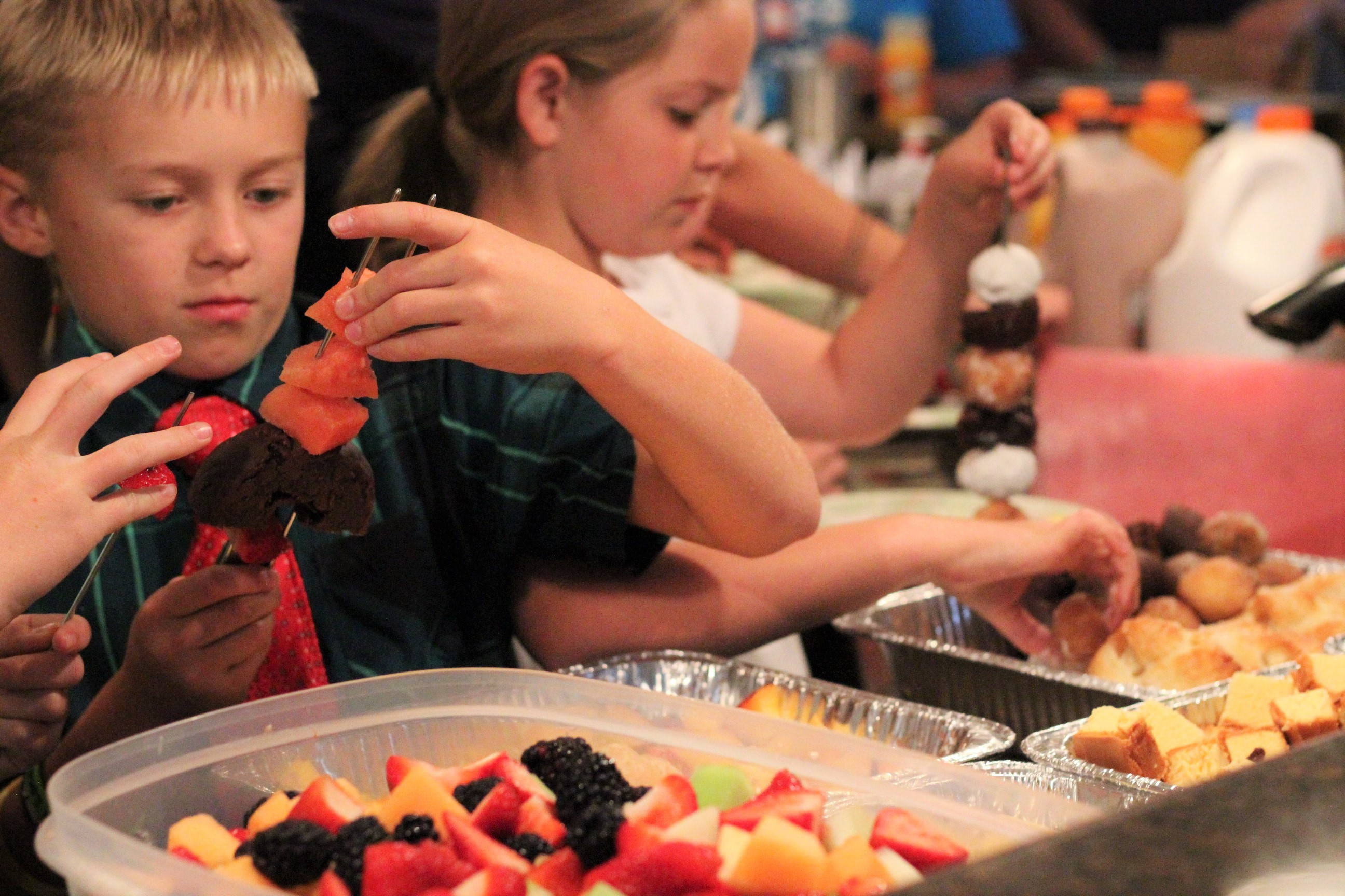 Two kids putting fruit and desserts on kebab skewers from containers full of fruit and desserts.