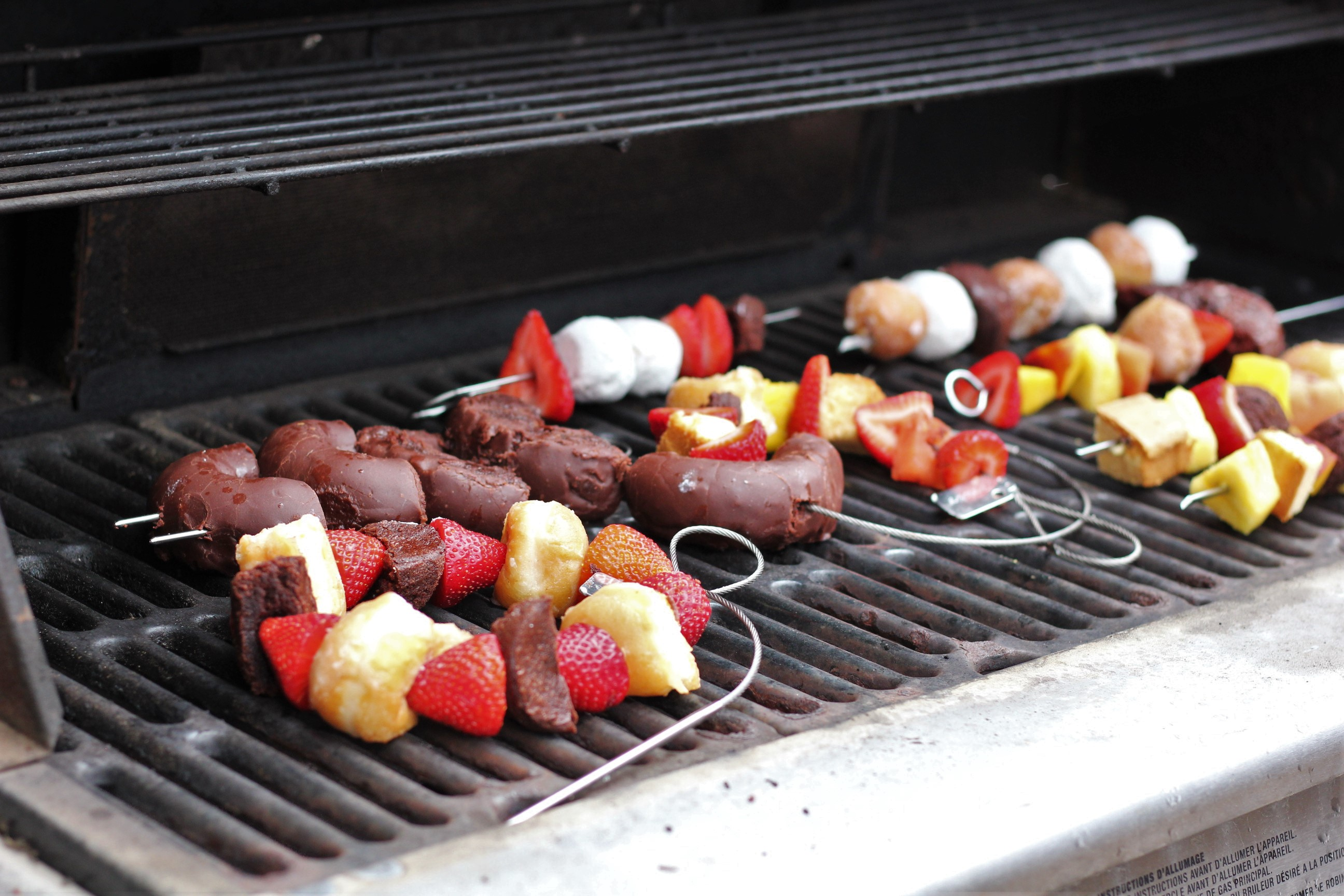 Dessert kebabs with donuts and fruit on a grill.