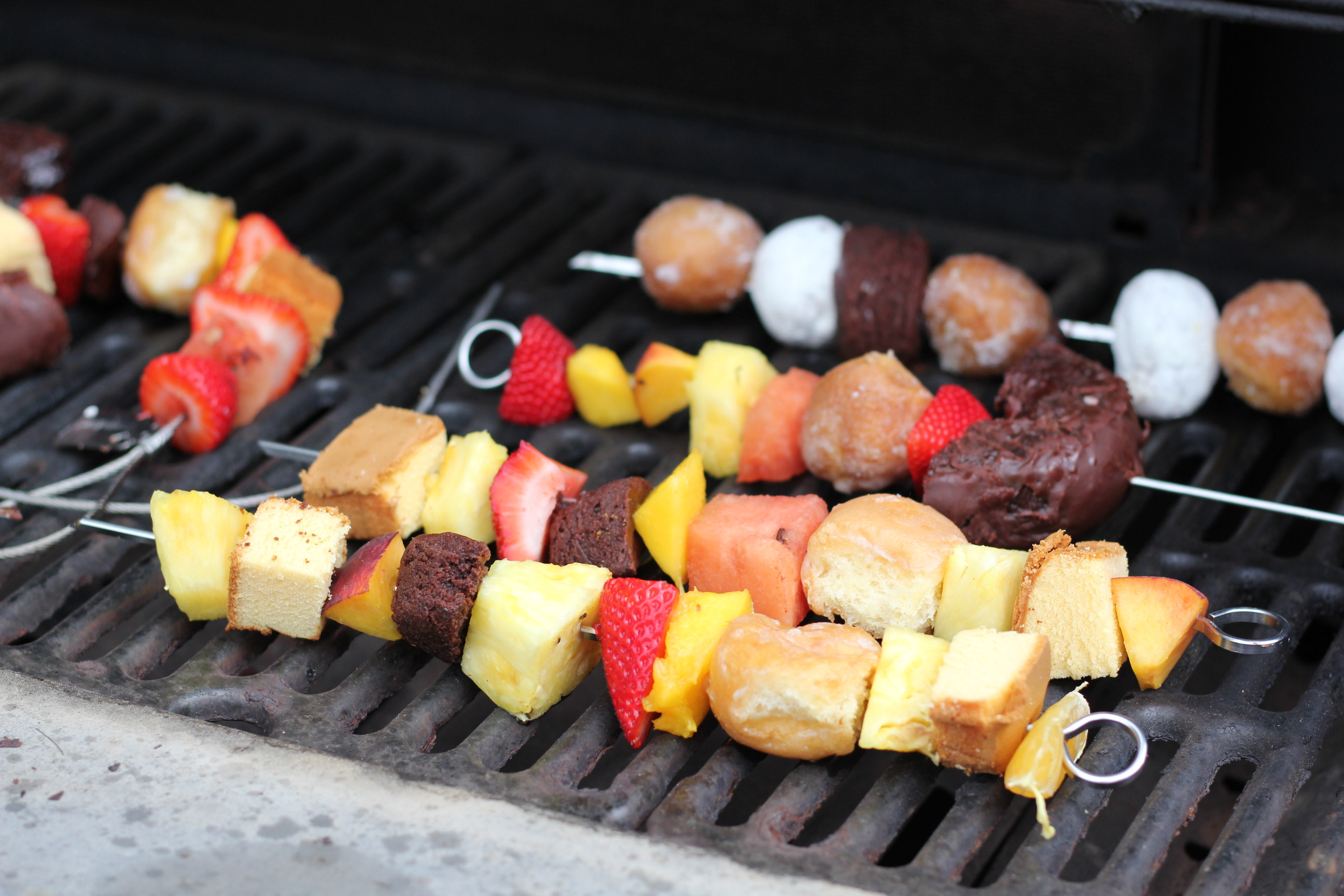 Donut and fruit dessert kebabs skewered on a grill.