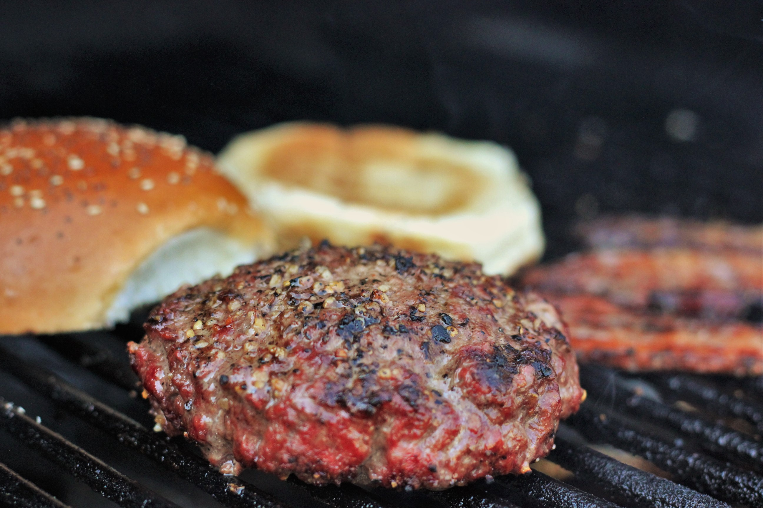 stuffed burger, buns, and bacon on the grill.
