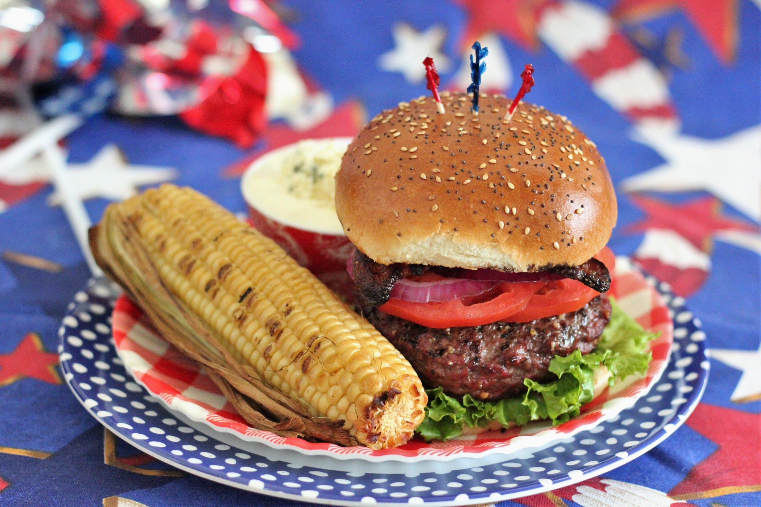 assembled stuffed burger on a red plate with whole grilled corn.