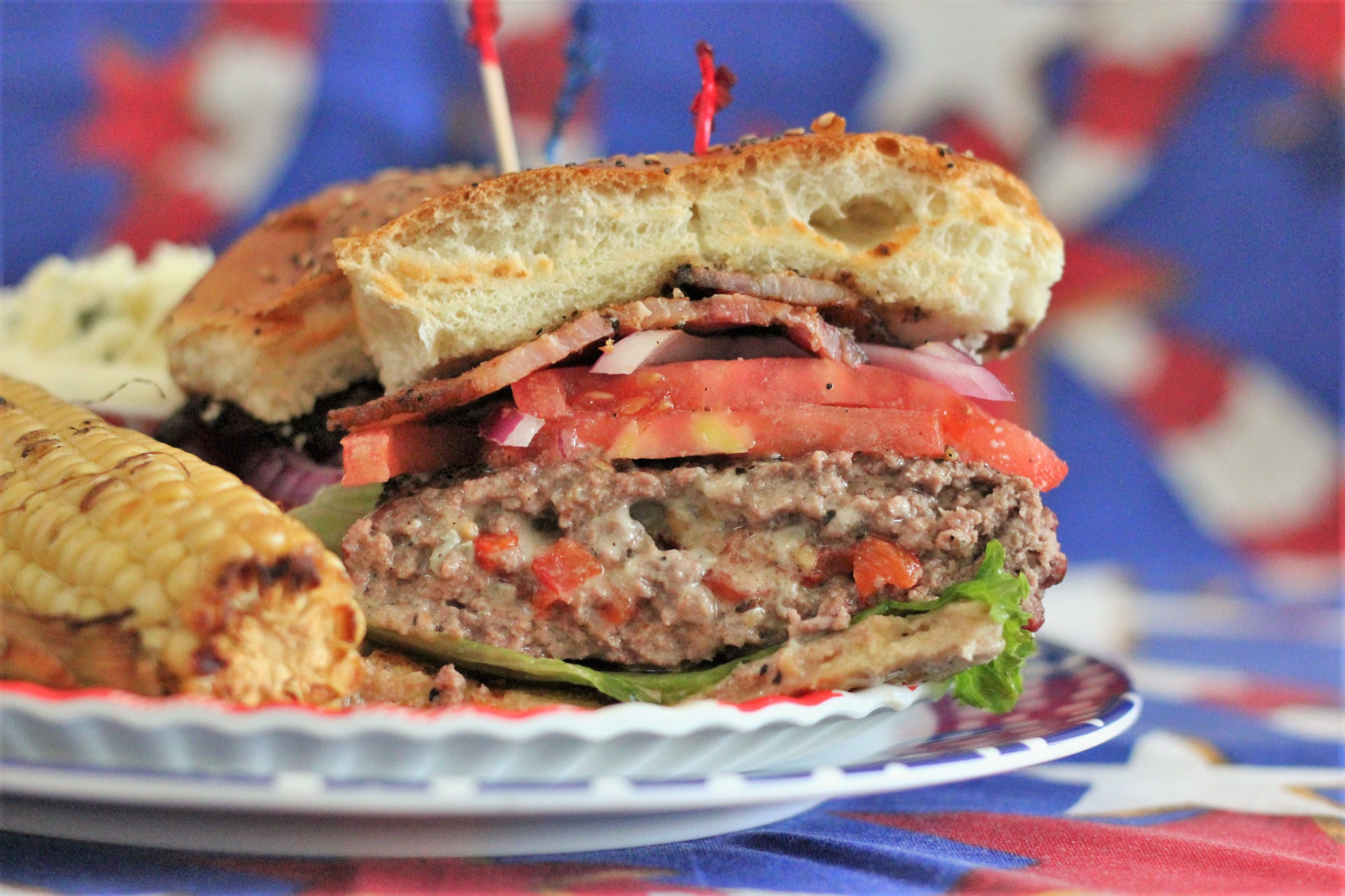 blue cheese stuffed burger on plate with grilled corn.