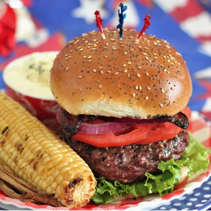 hamburger topped with lettuce, tomato, onion, bacon on a seeded bun, sitting on a plate next to a corn on the cob.