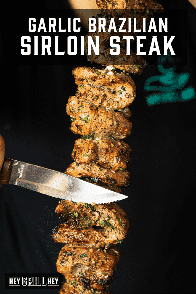 Knife slicing through marinated garlic Brazilian steaks on a skewer with text overlay - Garlic Brazilian Sirloin Steak.