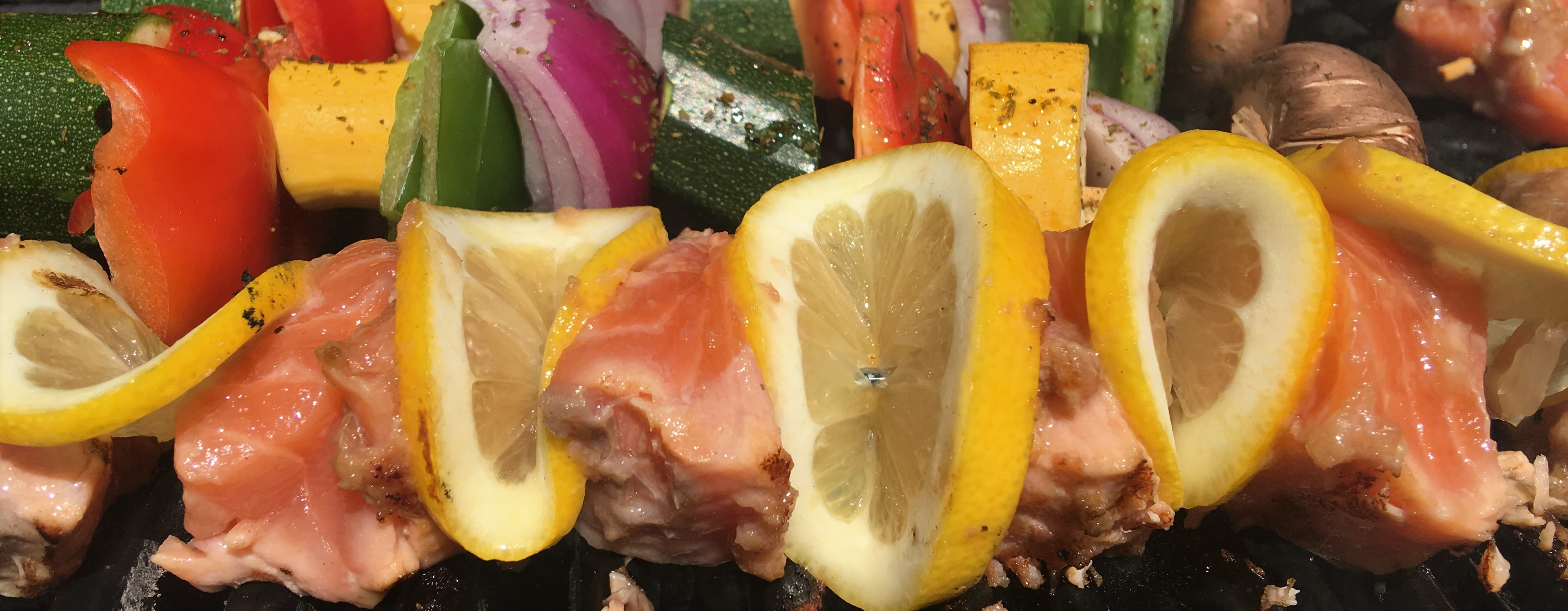 Raw salmon pieces threaded on a skewer in between lemon slices.