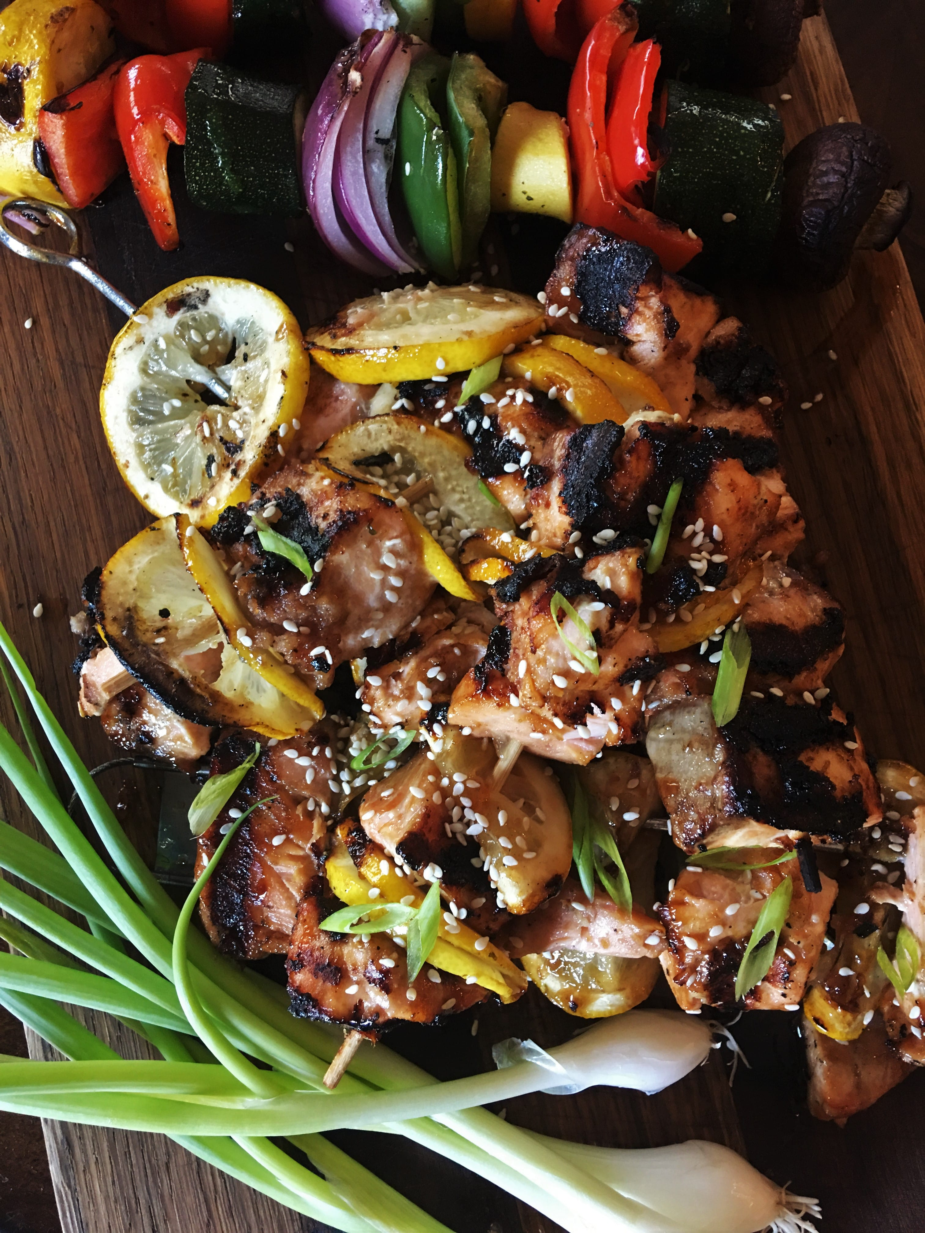 Sticky Bacon and Salmon Kebabs arranged in a pile on a wood cutting board next to fresh green onions and grilled vegetables.