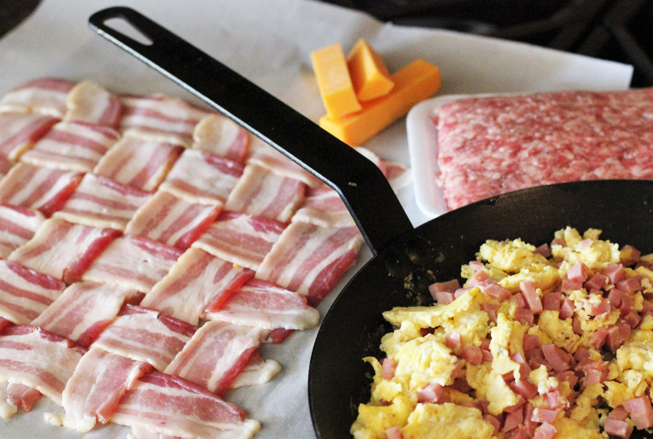 pan of eggs and ham next to a bacon weave on wax paper.