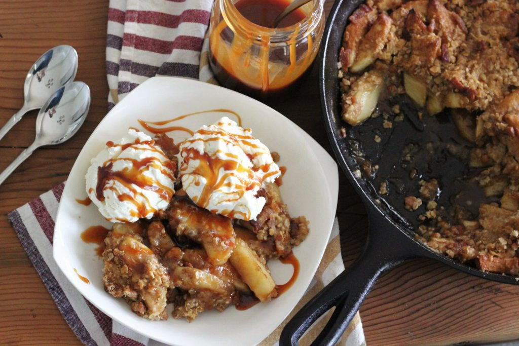 Arial view of Skillet Bacon Apple Crisp served on a white plate.