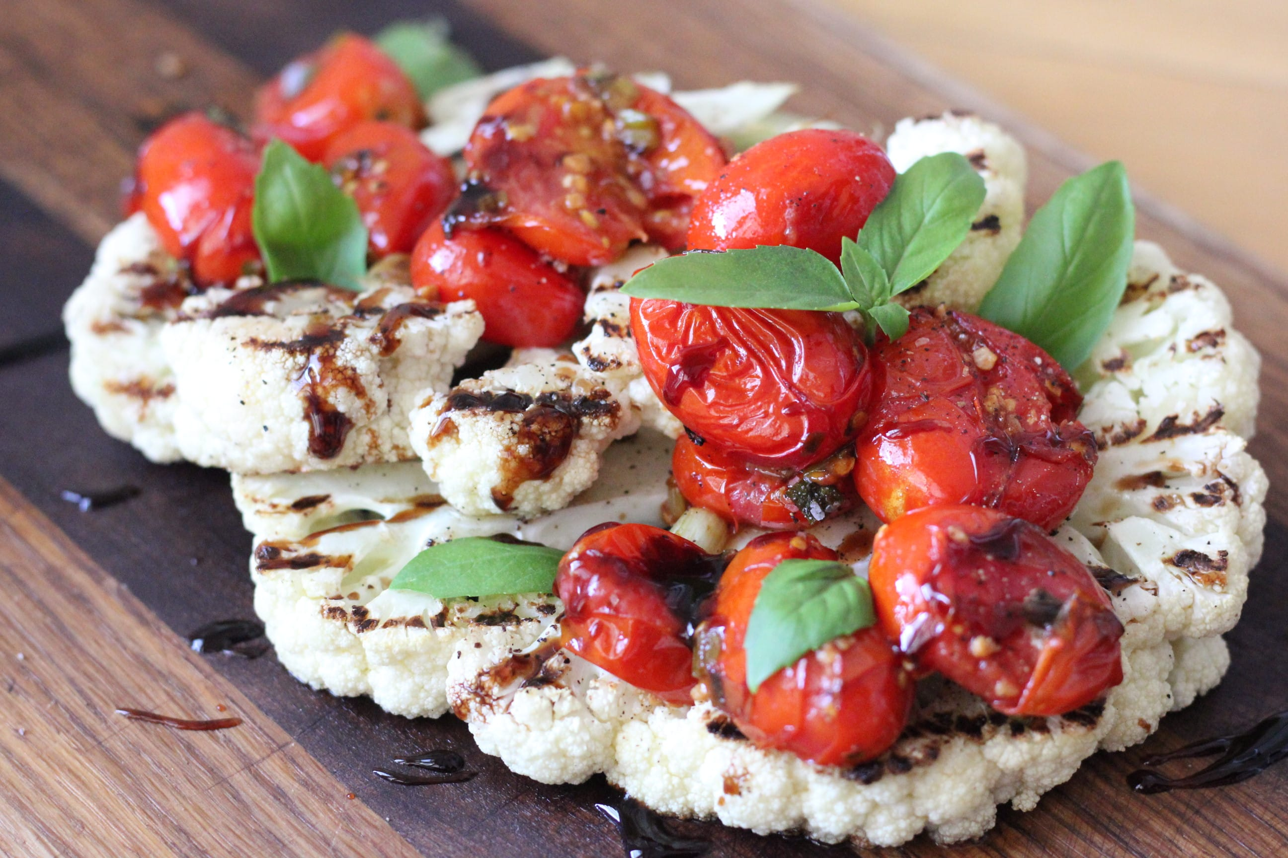 grilled cauliflower steaks with burst tomato salad on a wooden cutting board.