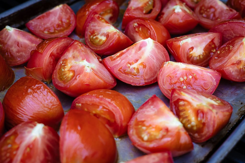 Sliced tomatoes on a baking dish.