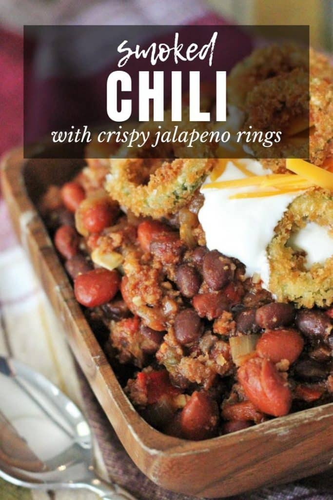 Smoked chili in a wood bowl topped with sour cream, cheese, and fried jalapeno rings