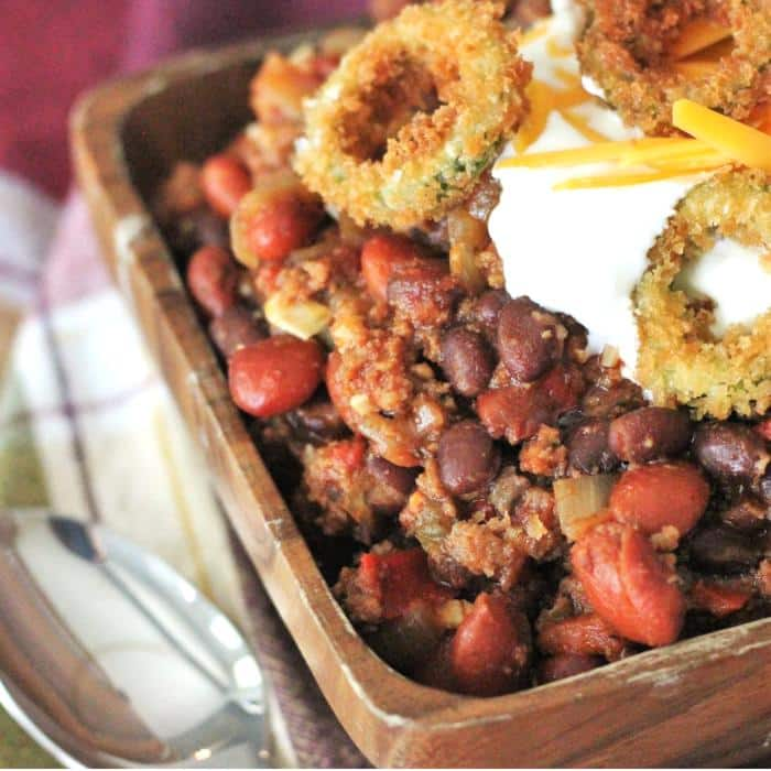 smoking hot chili in a bowl garnished in fried jalapeno rings