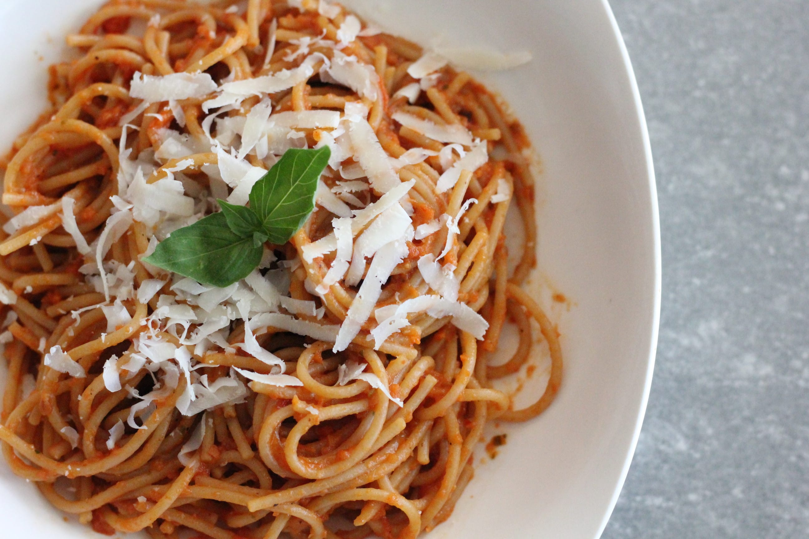 bowl of spaghetti noodles with roasted tomato sauce and topped with shredded cheese.