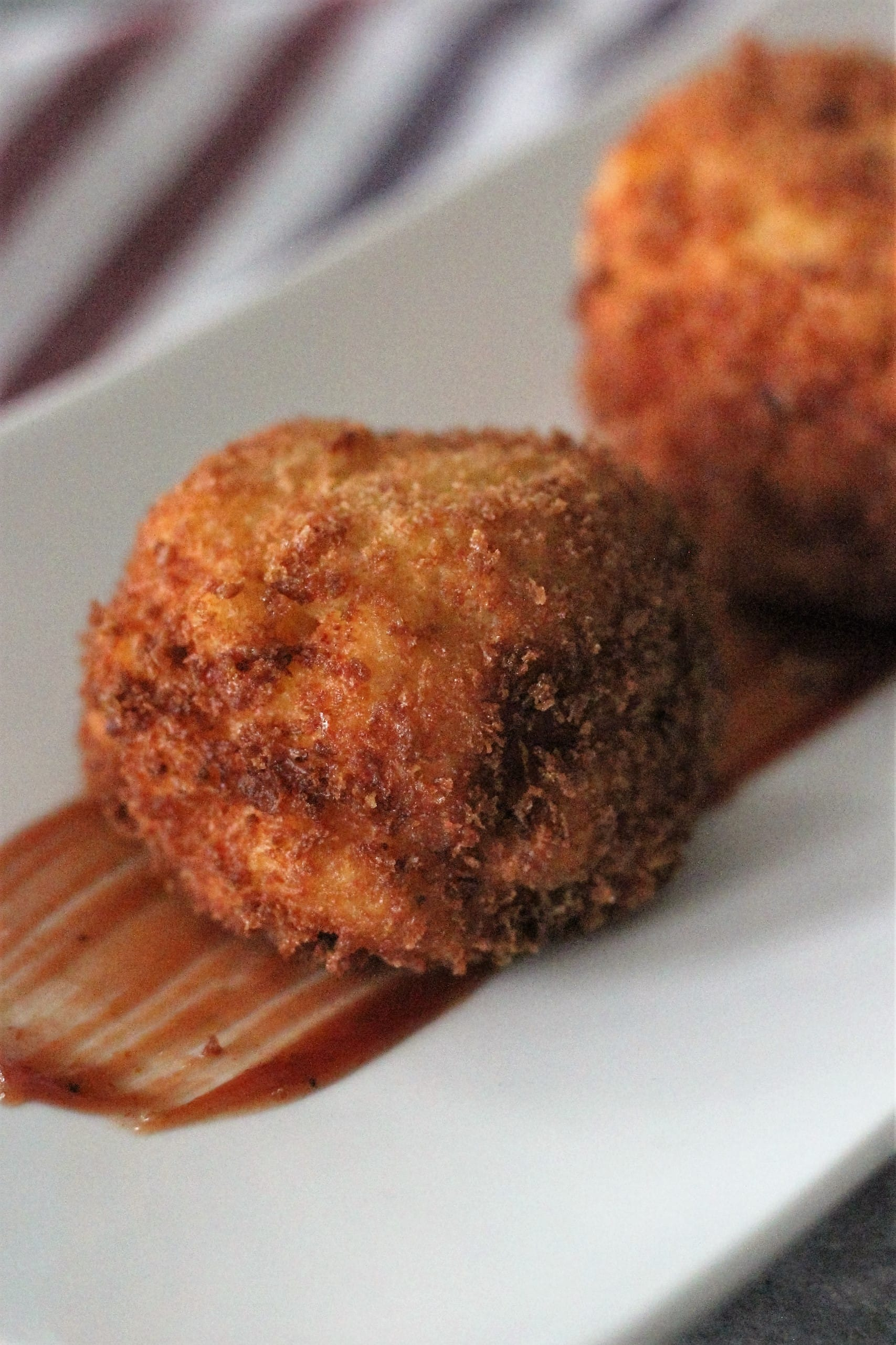 Pulled Pork Stuffed Mac and Cheese Bombs served on a white plate.