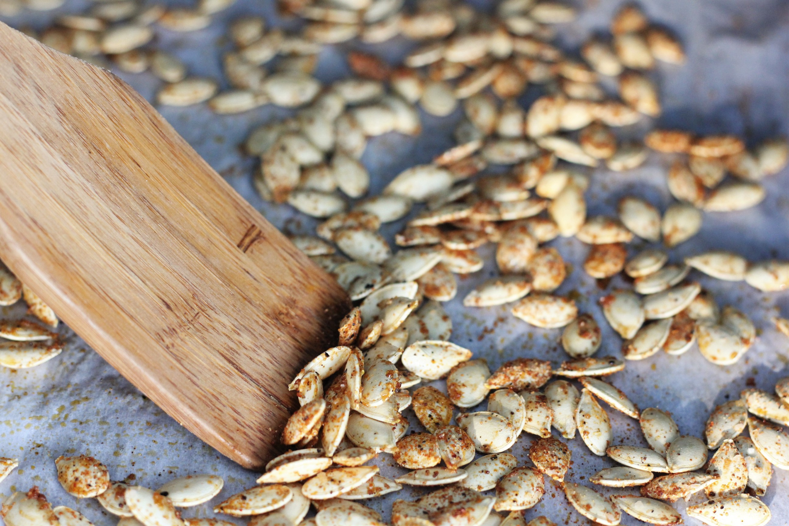 wooden spoon scraping bbq pumpkin seeds off parchment paper.