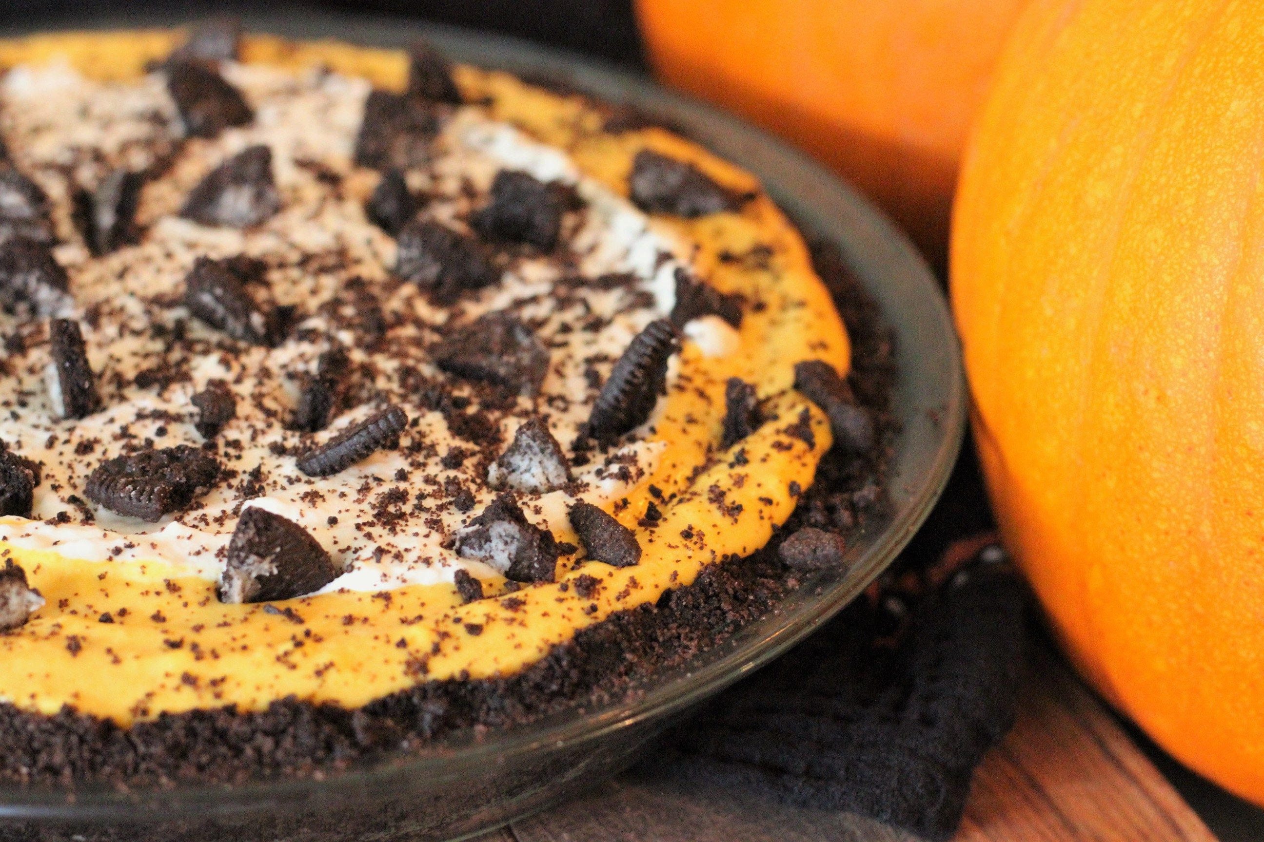 Roasted Pumpkin Cheesecake with a Cookie Crust next to two medium sized pumpkins.