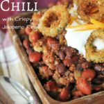 wooden bowl full of smoked chili topped with sour cream, cheddar cheese, and crispy jalapeno rings