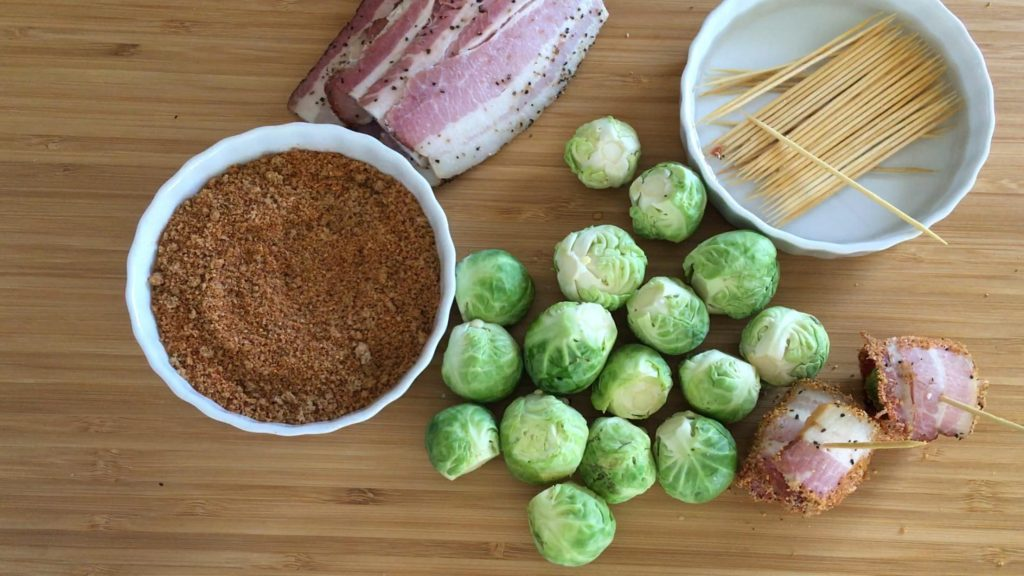 Whole brussels sprouts on a wooden cutting board surrounded by a bowl of BBQ rub, uncooked peppered bacon, long toothpicks soaking in a bowl of water, and two bacon wrapped brussels sprouts.