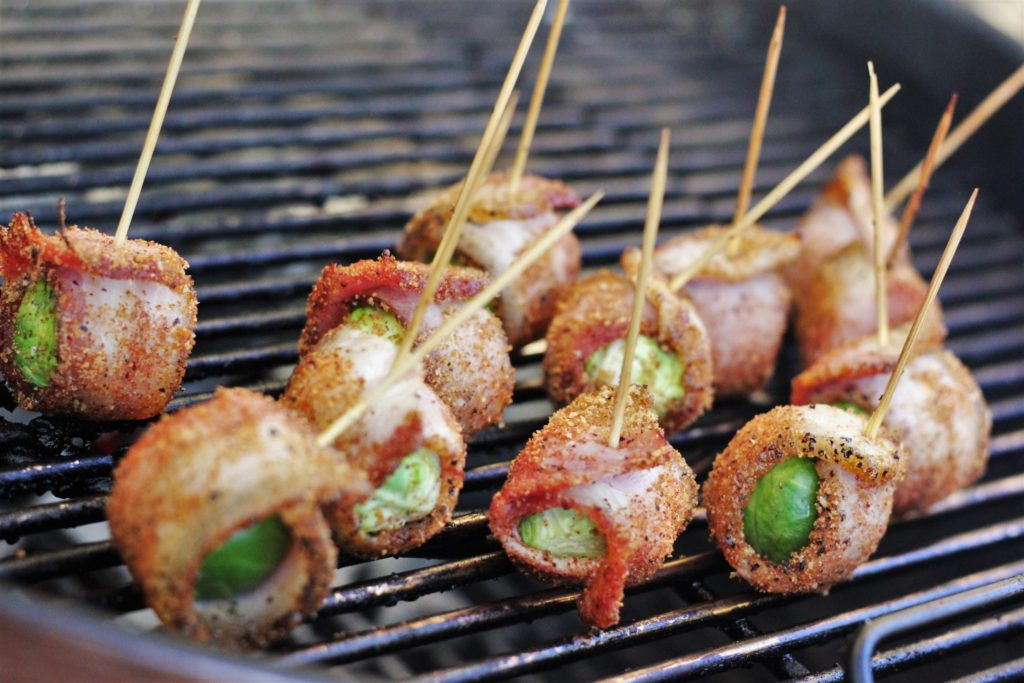 Bacon wrapped and seasoned brussels sprouts secured with long toothpicks on the grill grates of a charcoal grill.