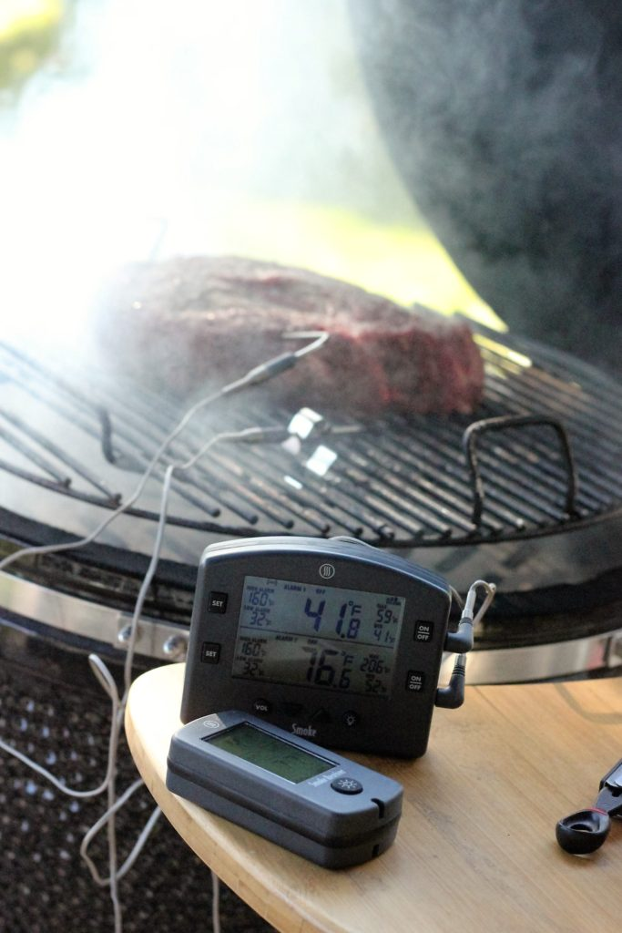 chuck roast on the smoker with a thermometer in the roast.