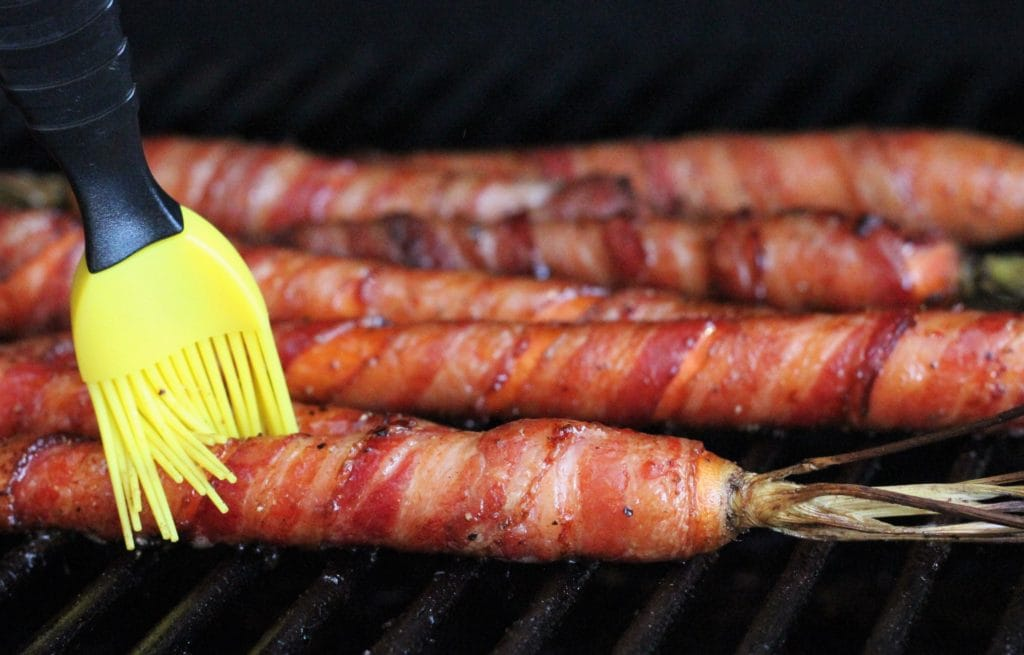 basting brush brushing maple syrup on a bacon wrapped carrot on the grill.