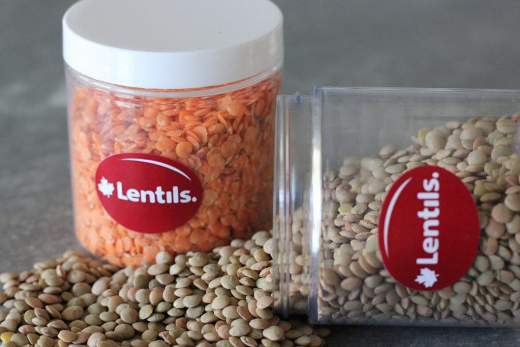 Two glass jars. One with red lentils, one with green lentils. The green lentils are tipped over and are spilling out.