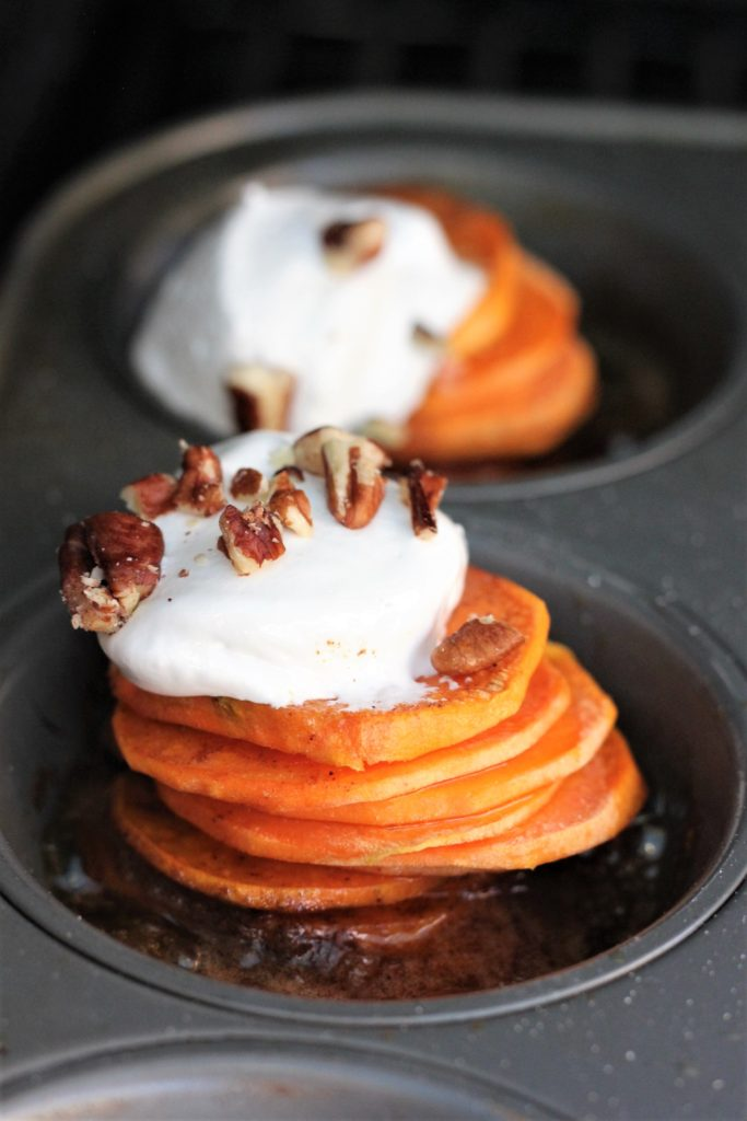 Two stacks of sliced sweet potatoes in a muffin tin, topped with a spoonful of marshmallow fluff and a half dozen chopped pecans.