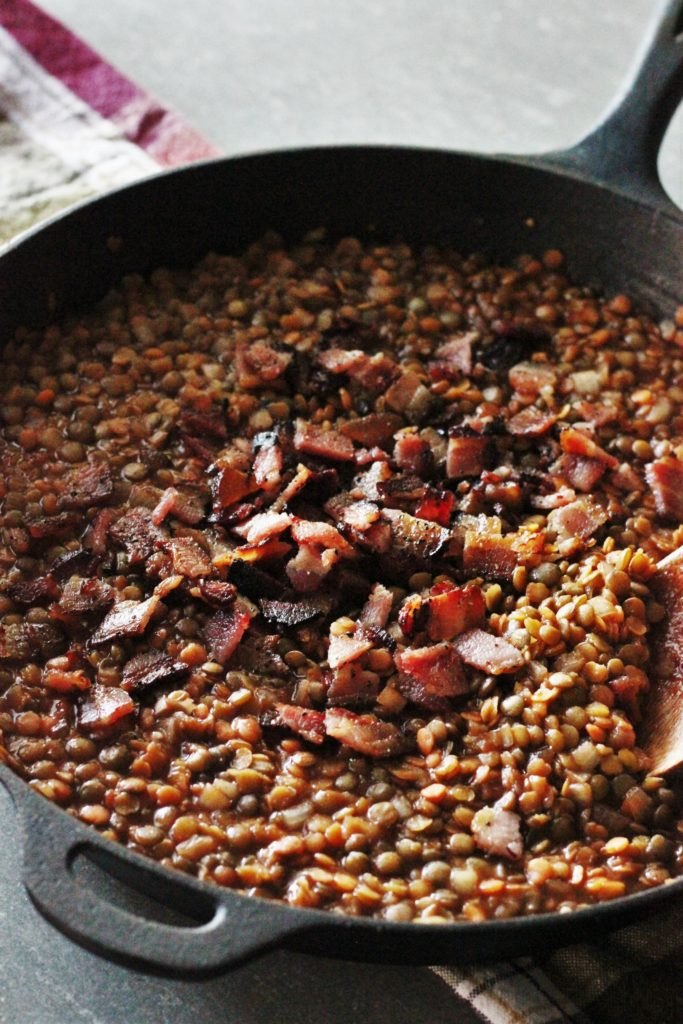 Smoky BBQ Baked Lentils with Bacon in a cast iron pan.