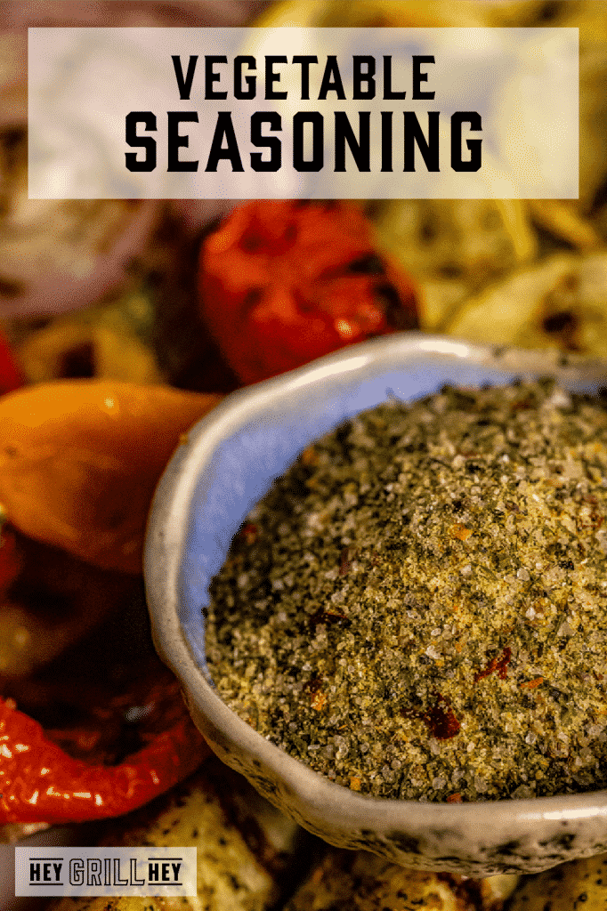 Homemade vegetable seasoning in a bowl with grilled vegetables in the background with text overlay - Vegetable Seasoning