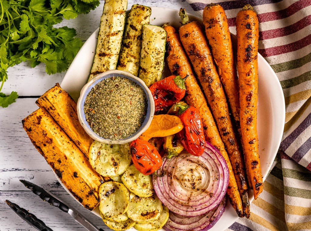 Vegetable seasoning in a small bowl surrounded by grilled vegetables.