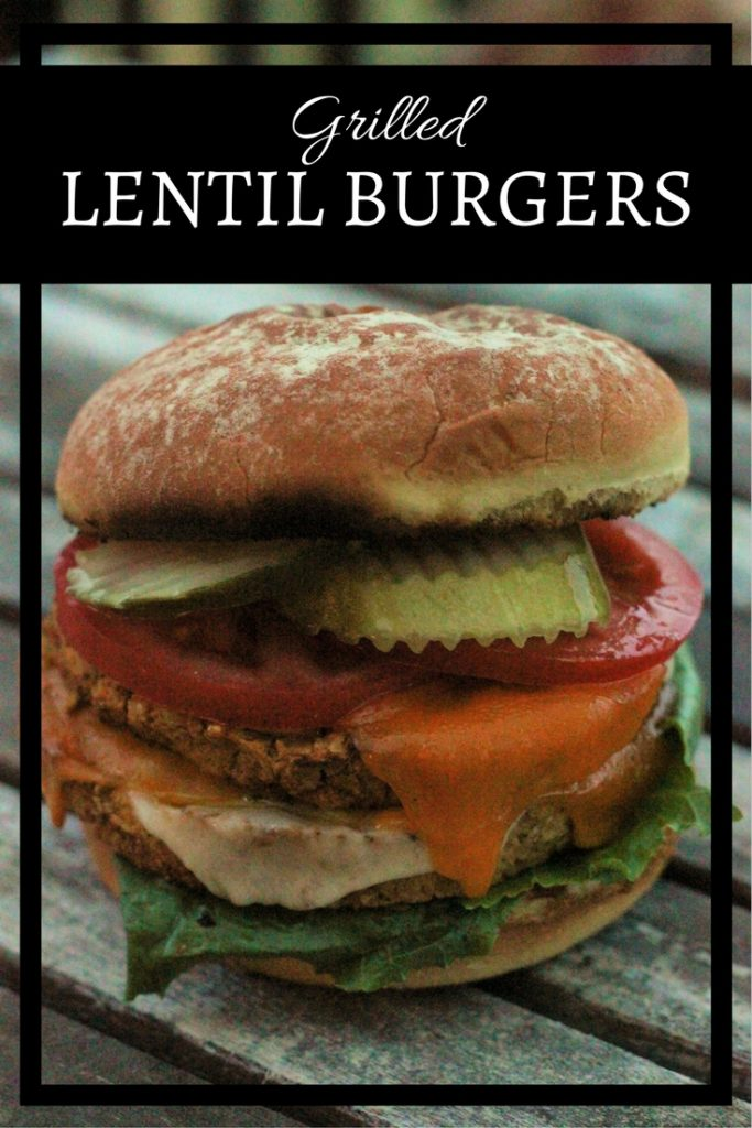 A Grilled Lentil Burger with lentil patty, lettuce, cheese tomatoes and pickles on a toaster hamburger bun.