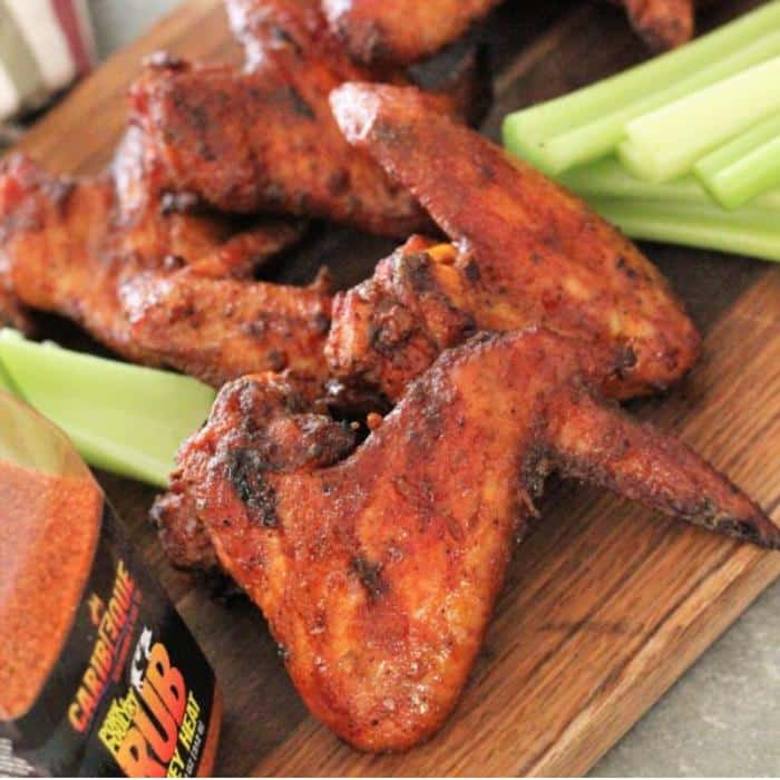 honey heat smoked chicken wings on a wooden cutting board next to sliced celery