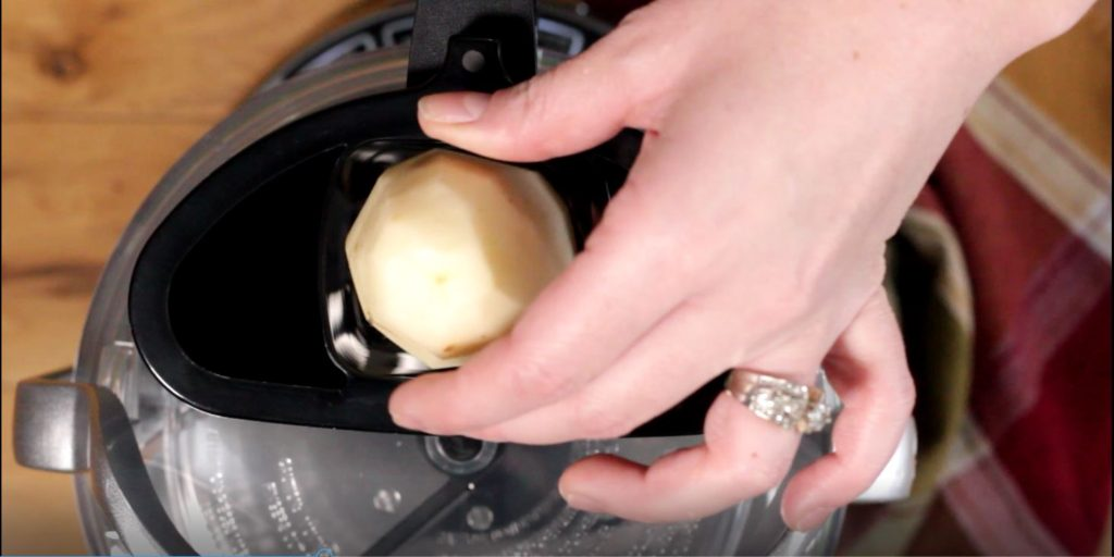 A hand placing a peeled potato in a machine used for slicing potatoes.