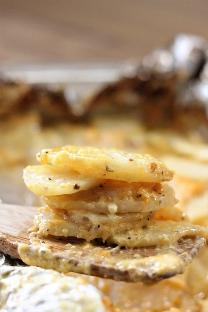 Closeup of a stack of sliced smoked chantilly potatoes on a wooden spoon.